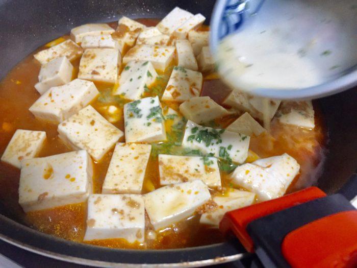 麻婆豆腐にとろみを加える。