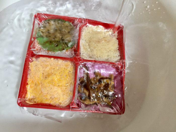 冷凍鶏飯の具材を流水解凍する。