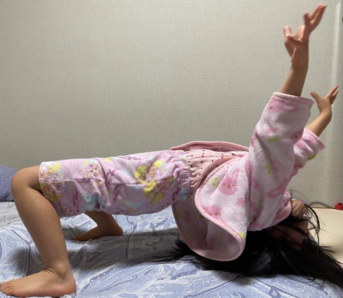 ふざけてブリッジの練習をする5歳の娘