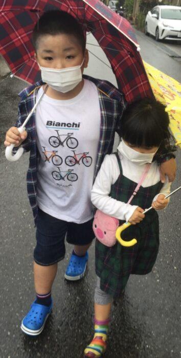 雨の日に傘を差して散歩する息子と娘